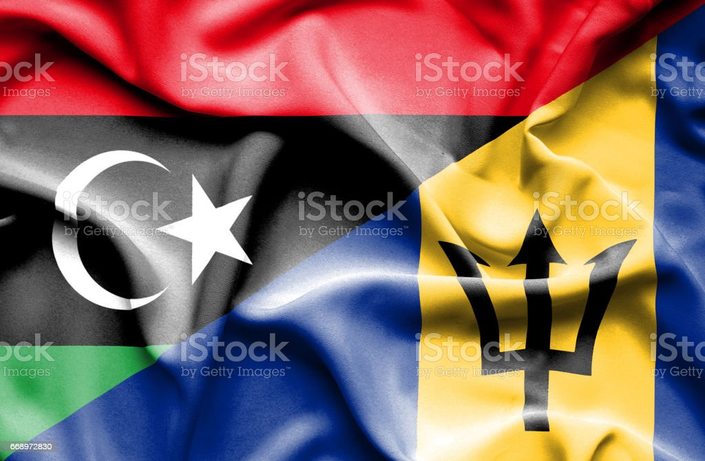 Waving flag of Barbados and Libya stock photo
