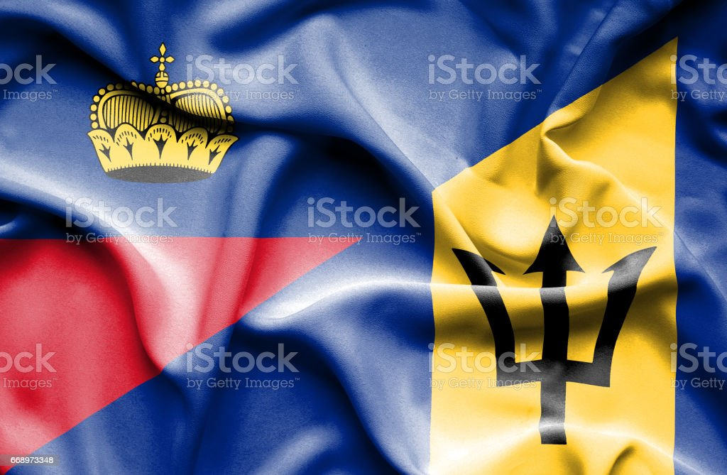 Waving flag of Barbados and Lichtenstein stock photo
