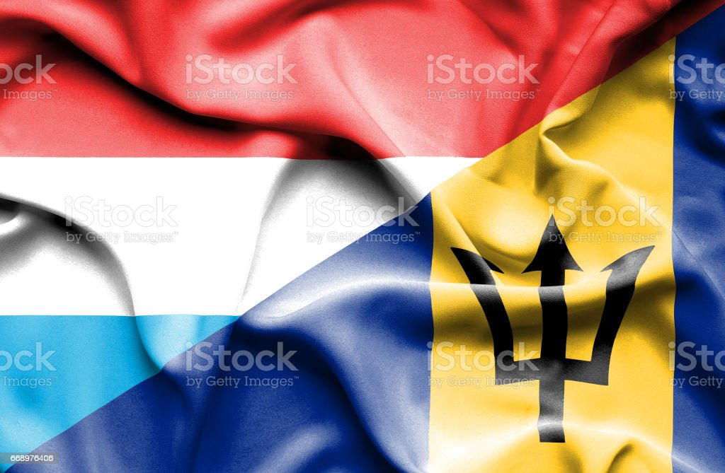 Waving flag of Barbados and Luxembourg stock photo