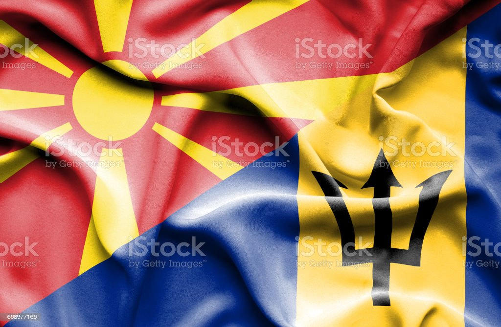 Waving flag of Barbados and Macedonia stock photo