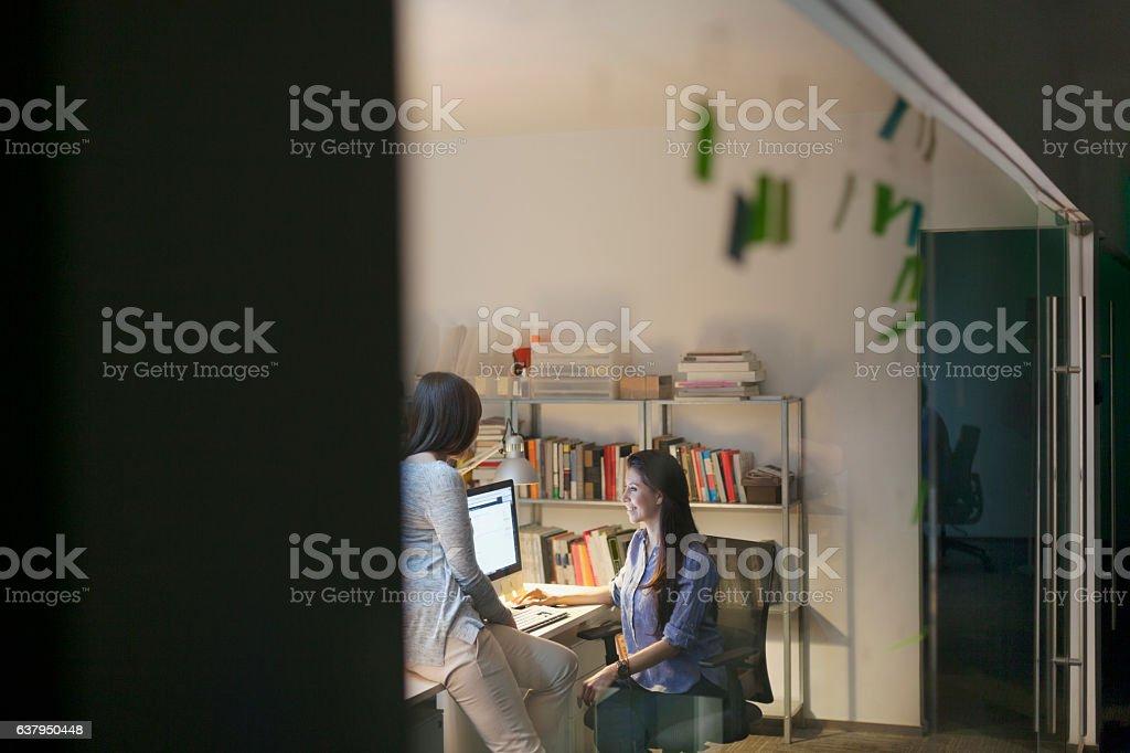Women working together in design studio at night vector art illustration