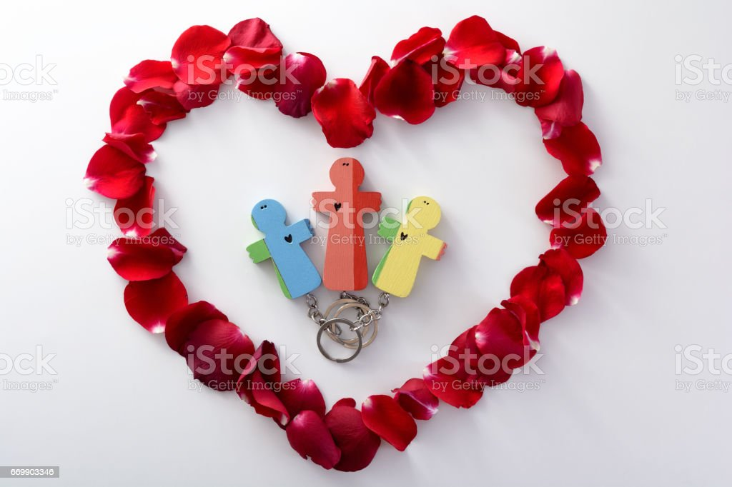 Wooden figures of the family into heart from rose petals. Mother with her children stock photo