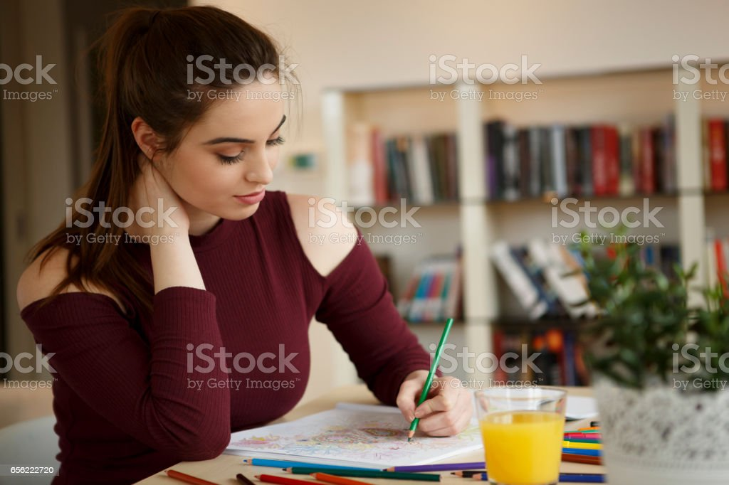 Young woman relaxing at home by coloring book vector art illustration