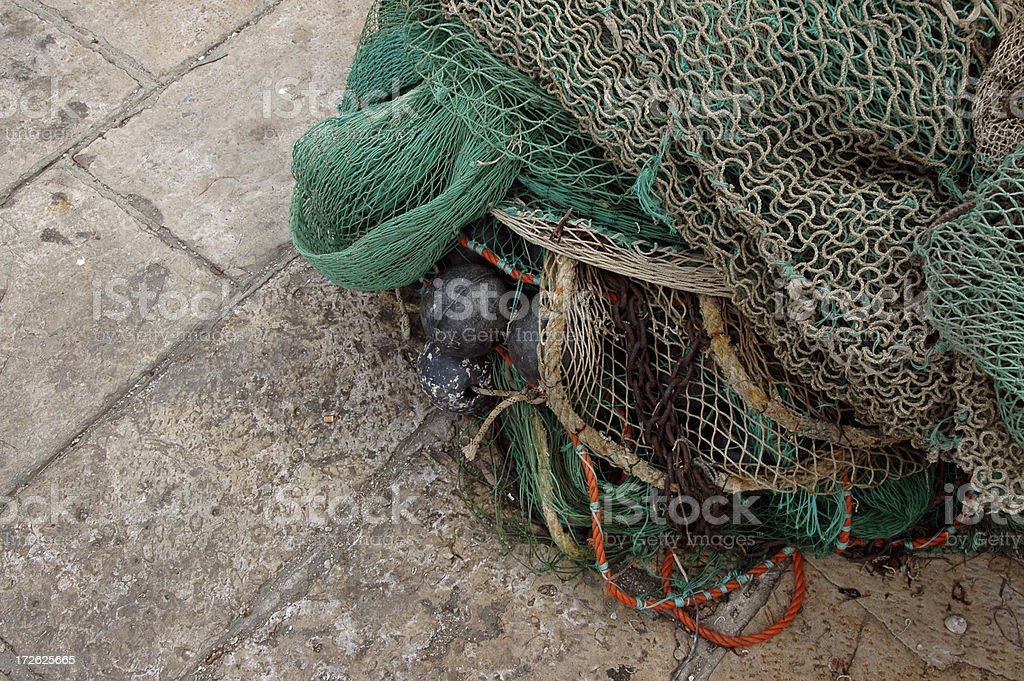 FISHING NETS ON HARBOUR FLAGSTONES royalty-free stock photo