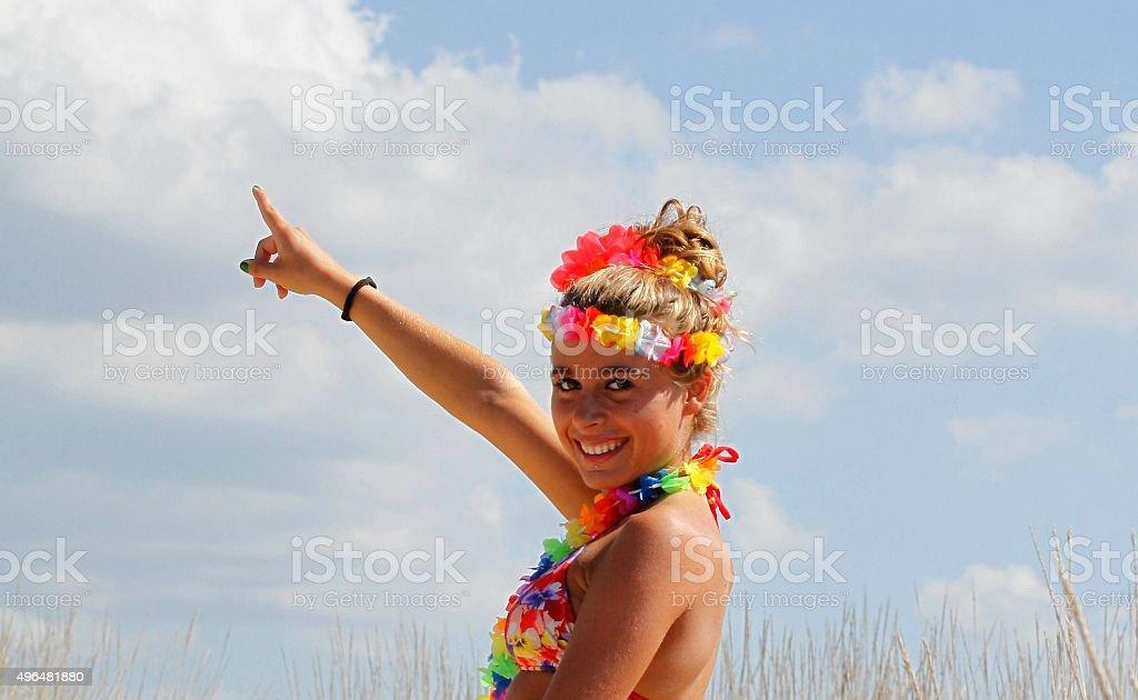 GIRL DRESSED HAWAIIAN BEACH POINTING TO HEAVEN stock photo