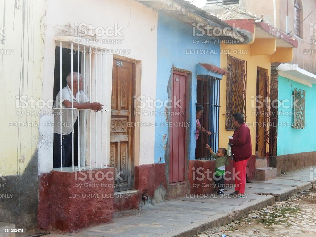 CUBANS TALKING THROUGH SECURITY DOOR GATE, TRINIDAD, CUBA stock photo