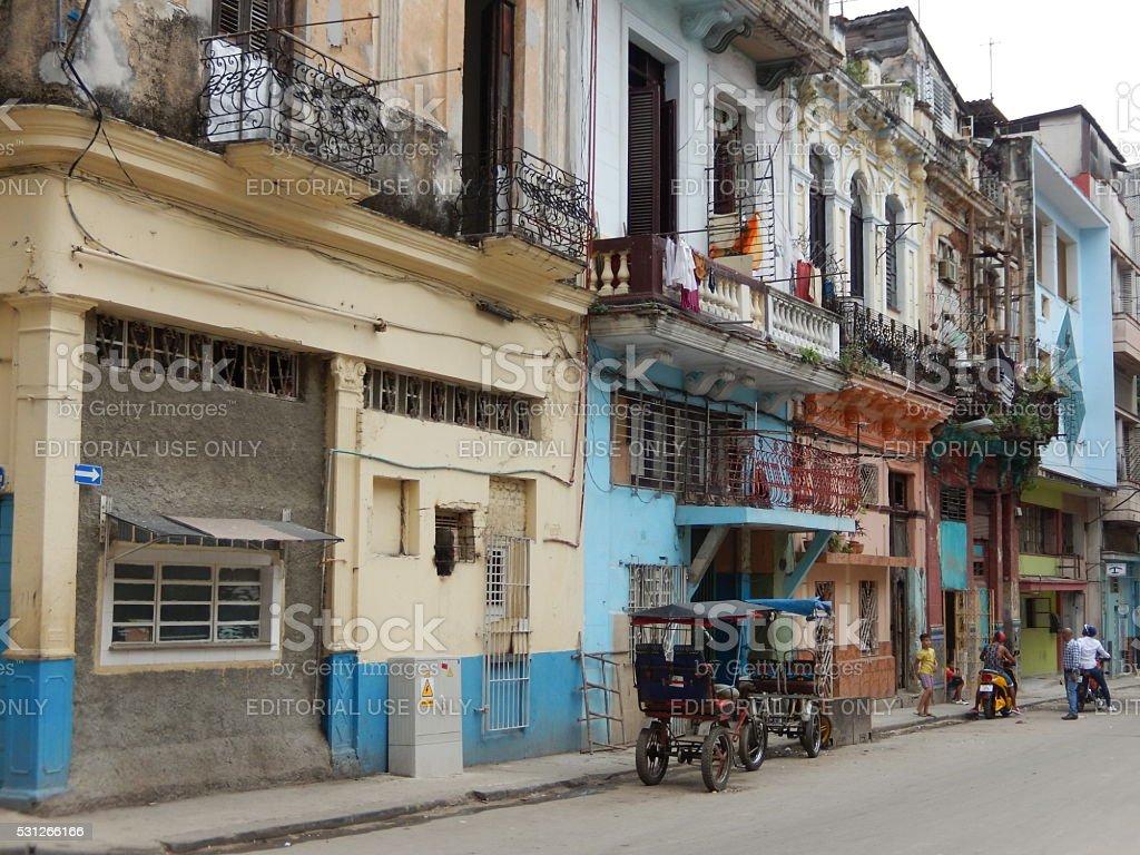 TAXI RICKSHAWS AND COLORFUL FACADES, HAVANA, CUBA stock photo