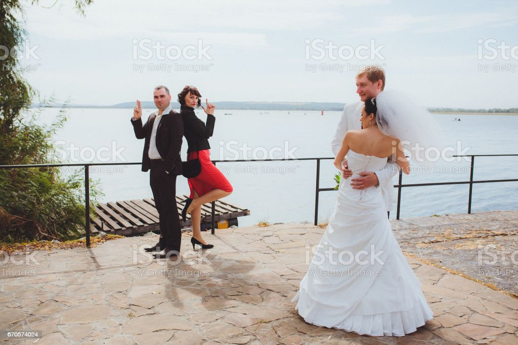 Весёлая свадьба. Счастливые молодые и красивые жених и невеста с друзьями stock photo