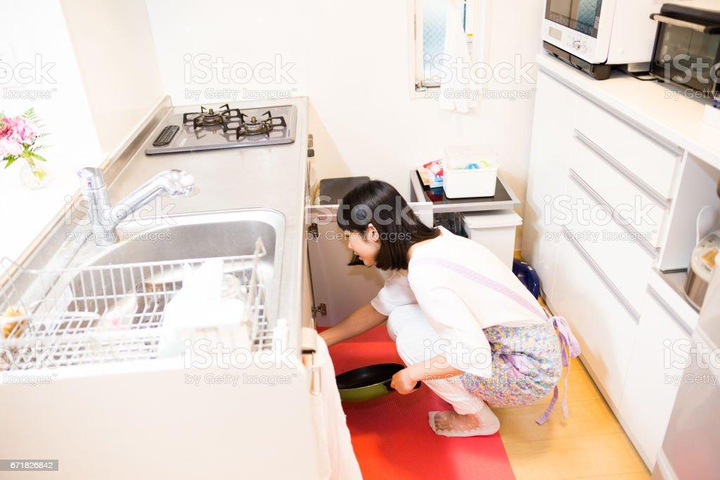 明るいキッチンに屈む日本人女性 stock photo