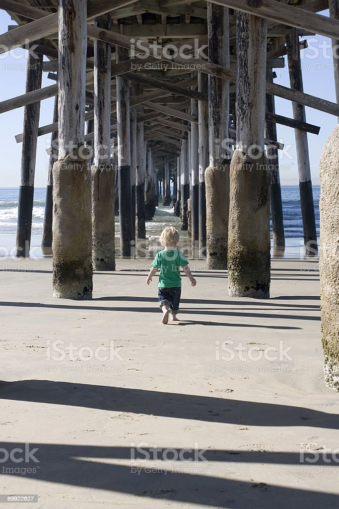 BOY WALKS UNDER PIER stock photo