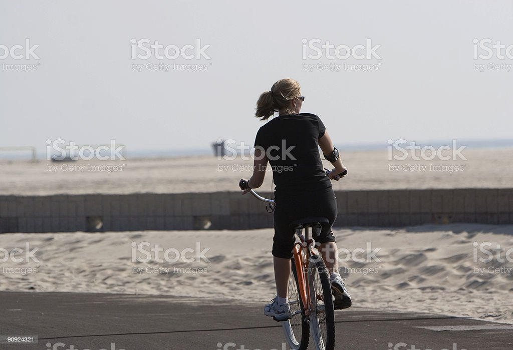 WOMEN RIDES ON A BEACH TRAIL royalty-free stock photo