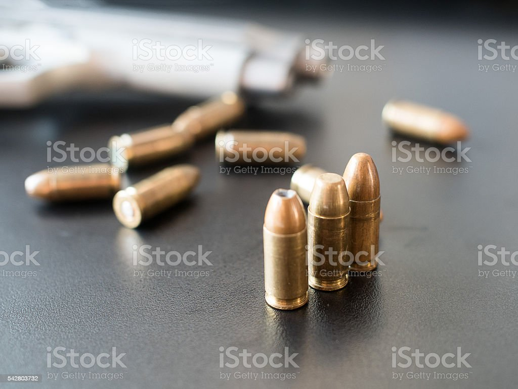 11mm bullets and short gun on black background. (selective focus) stock photo