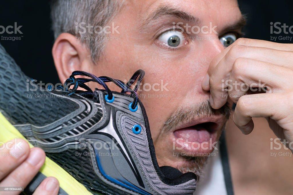 150609_ManGagsAfterSmellingShoe stock photo