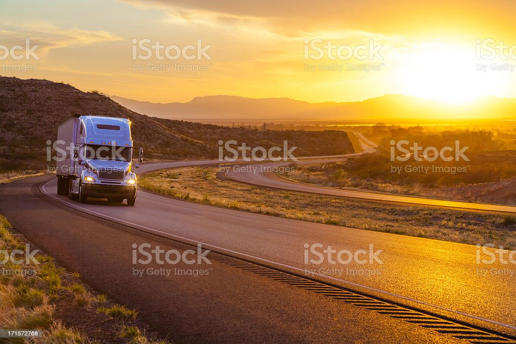 18-wheeler on interstate highway at sunset stock photo