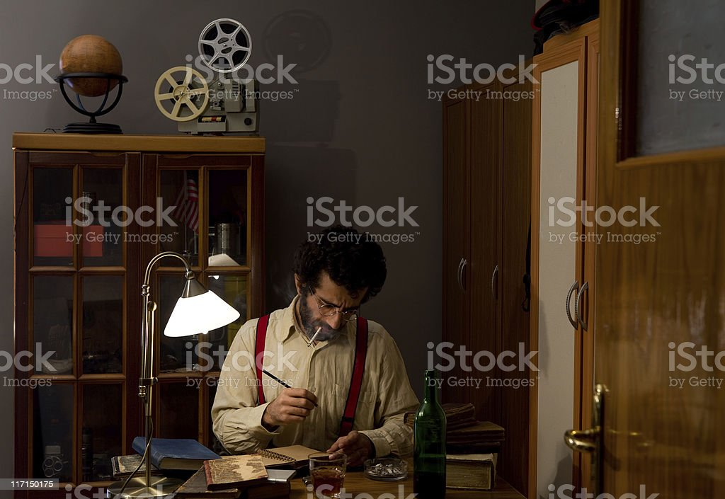 1930s writer in suspenders with film paraphernalia. stock photo