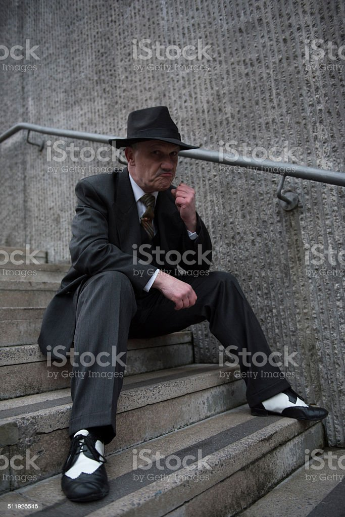 1940s gangster character sitting on steps outdoors stock photo
