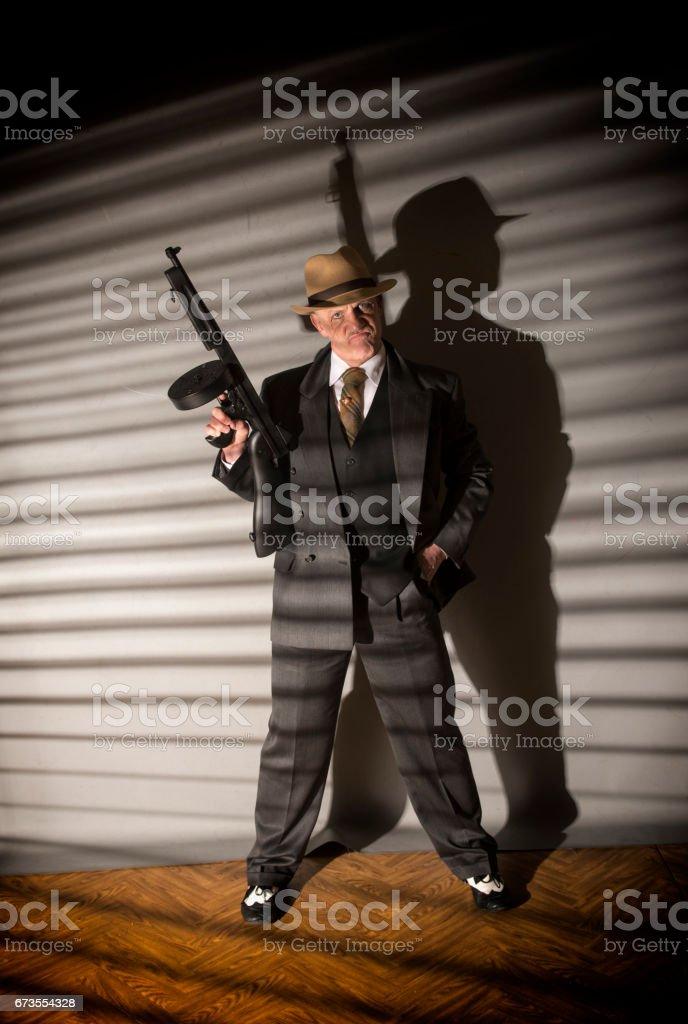 1940s gangster holding a machine gun stock photo
