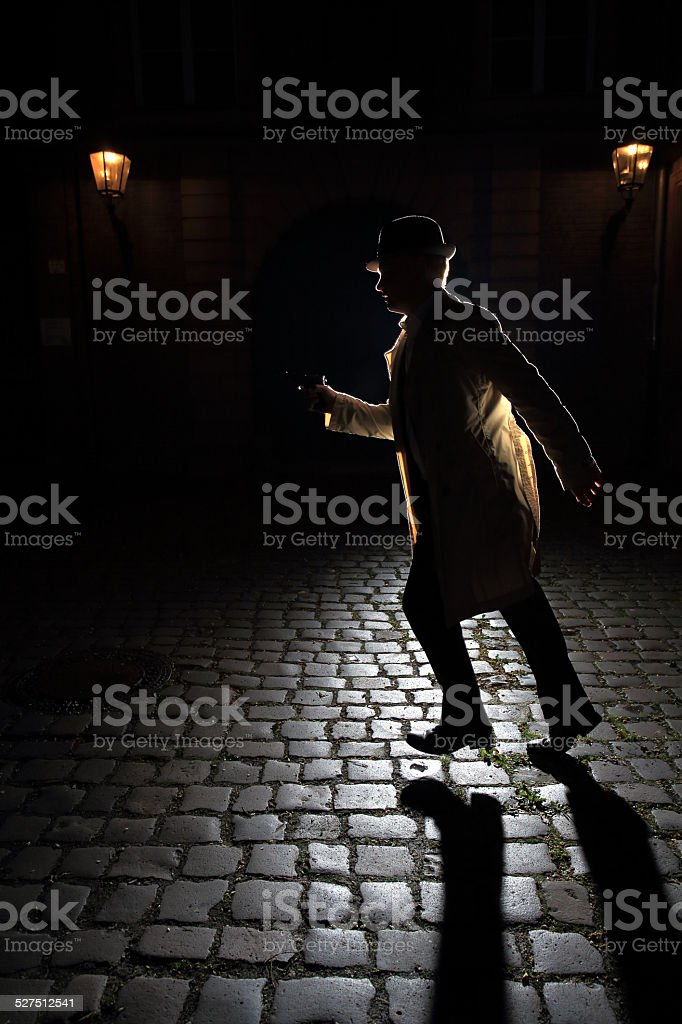 1940s retro gangster running with a gun stock photo