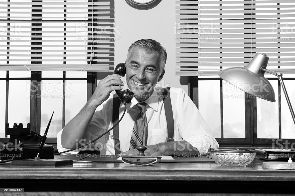 1950s smiling businessman on the phone stock photo