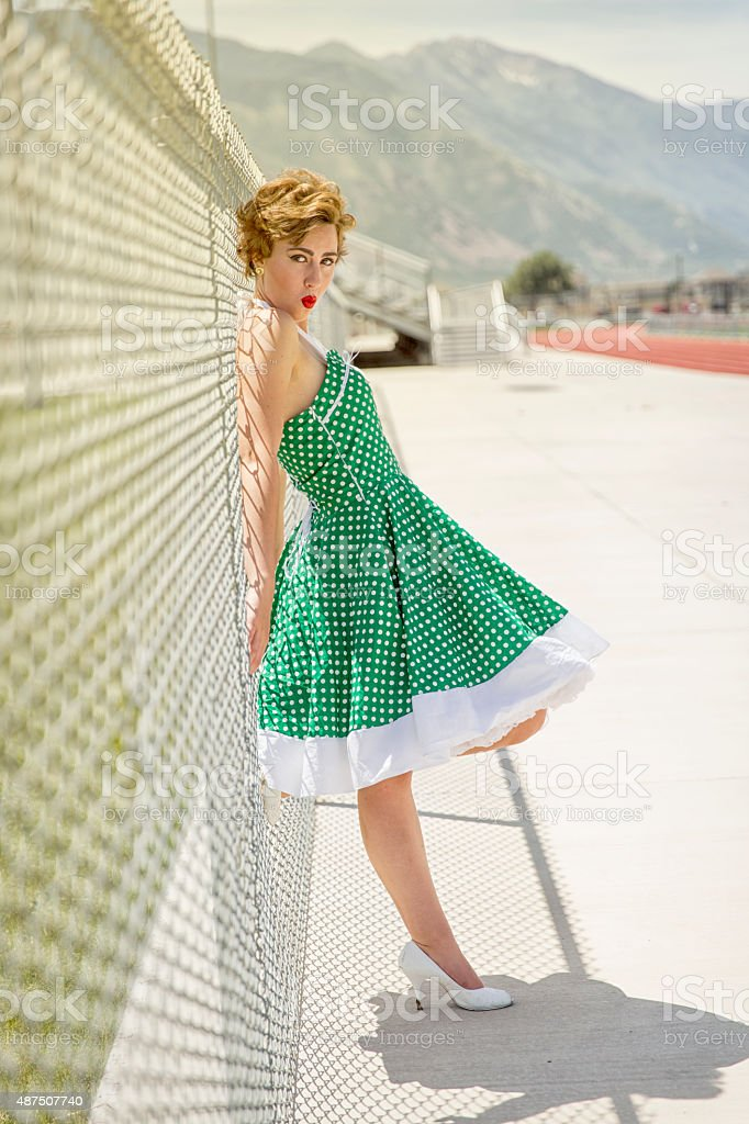 1950s Woman Leaning on a Chainlink Fence Making Kissing Face stock photo