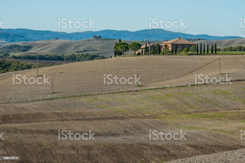 VAL D'ORCIA, TUSCANY-ITALY, OCTOBER 30, 2017:Classic view of scenic Tuscany landscape with famous farmhouse amidst idyllic rolling hills and valleys in autumn, Val d'Orcia, Italy stock photo