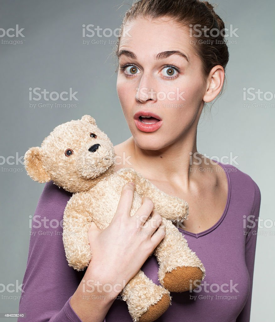 20s girl holding loving comforter surprised to be seen stock photo