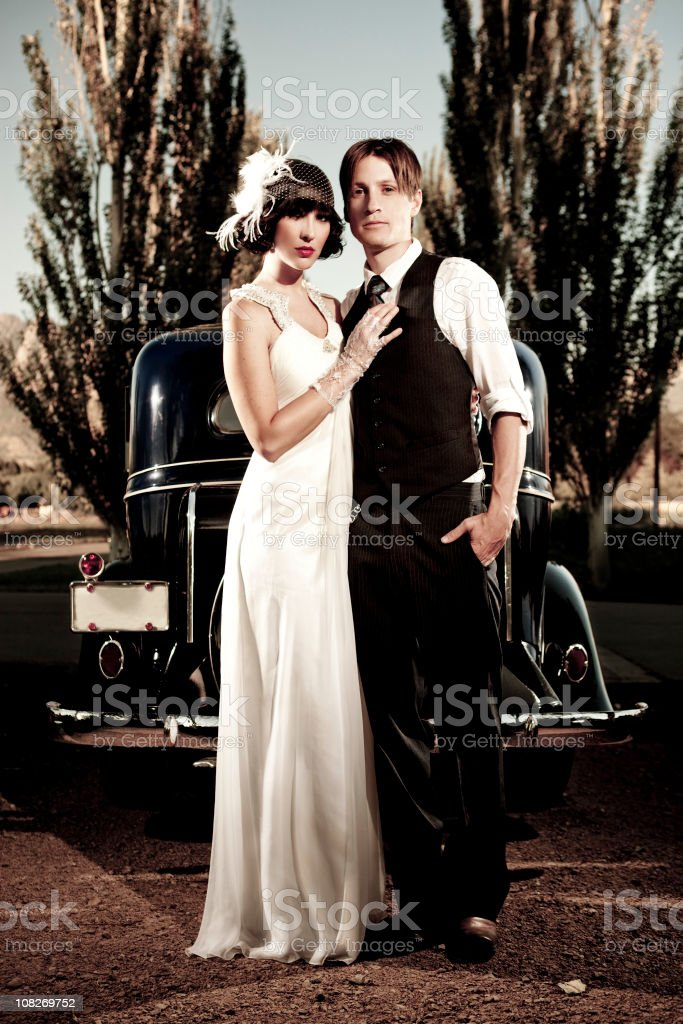 20s style couple standing in front of vintage car royalty-free stock photo