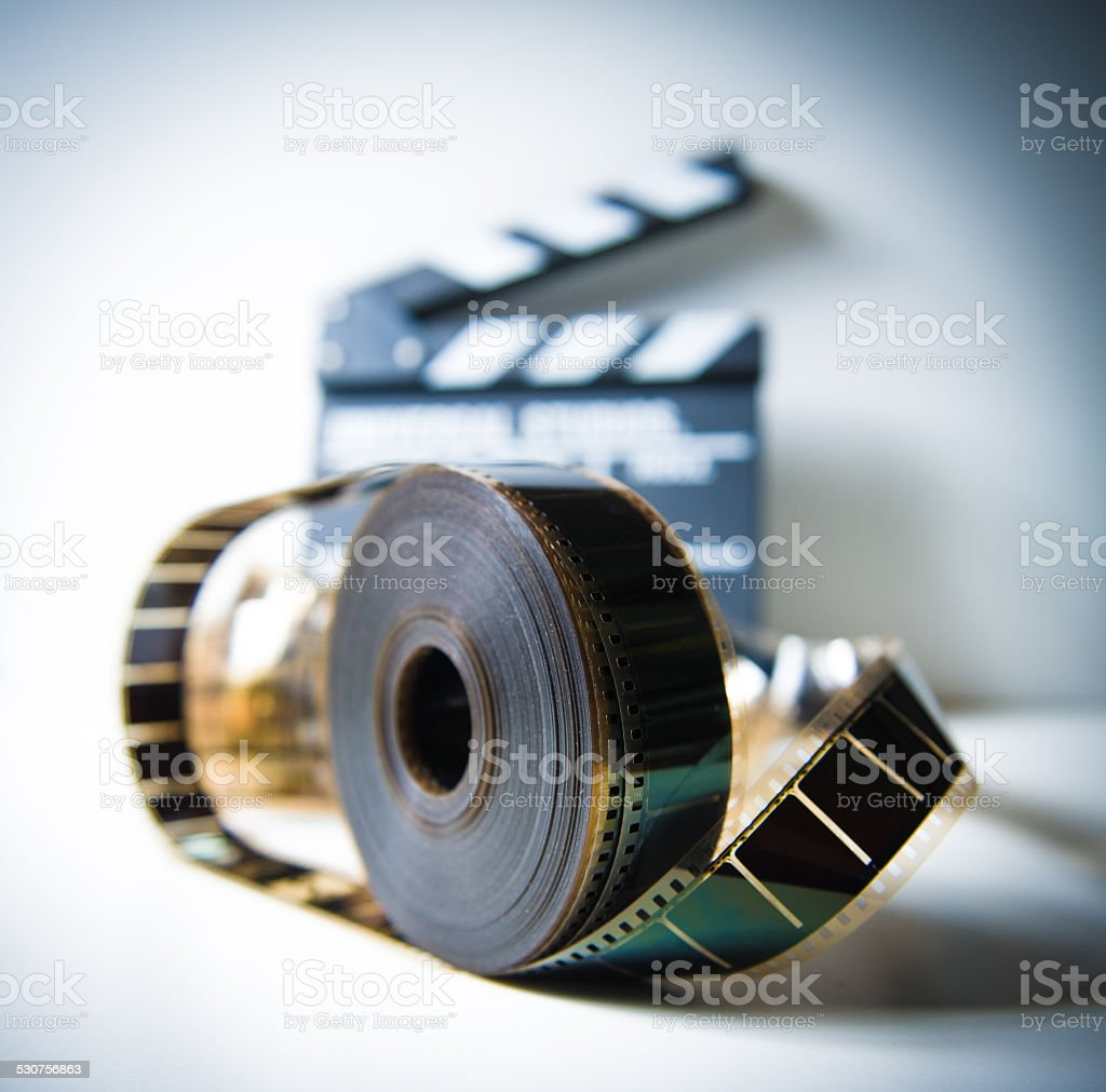 35mm movie reel with out of focus clapper in background stock photo