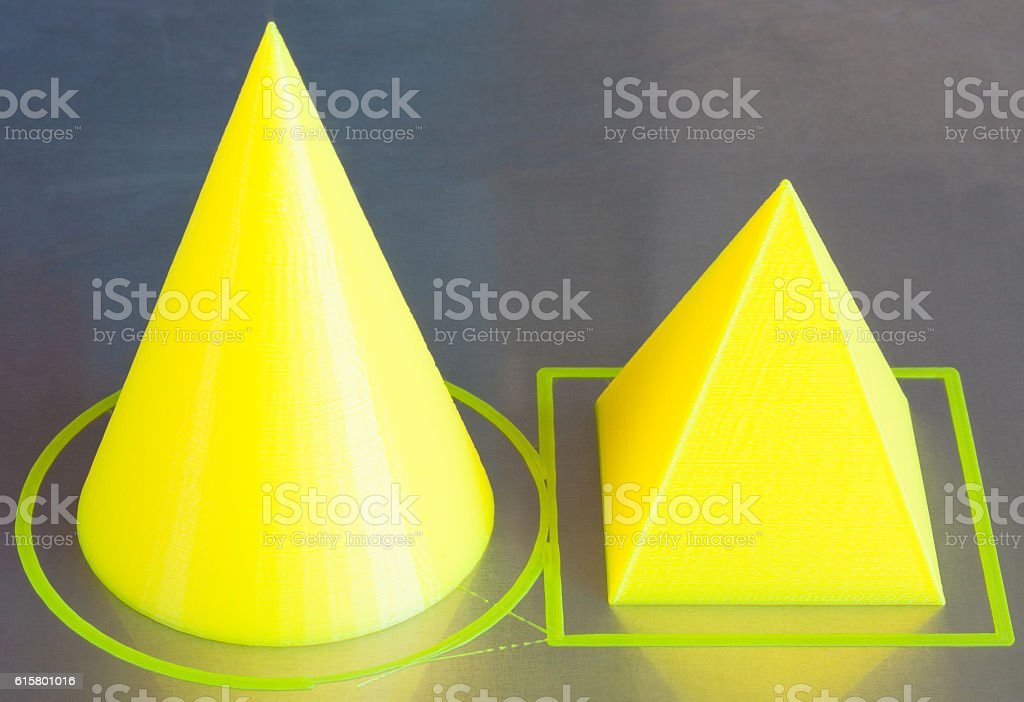 3d printed figures of cone and pyramide. Yellow filament. stock photo