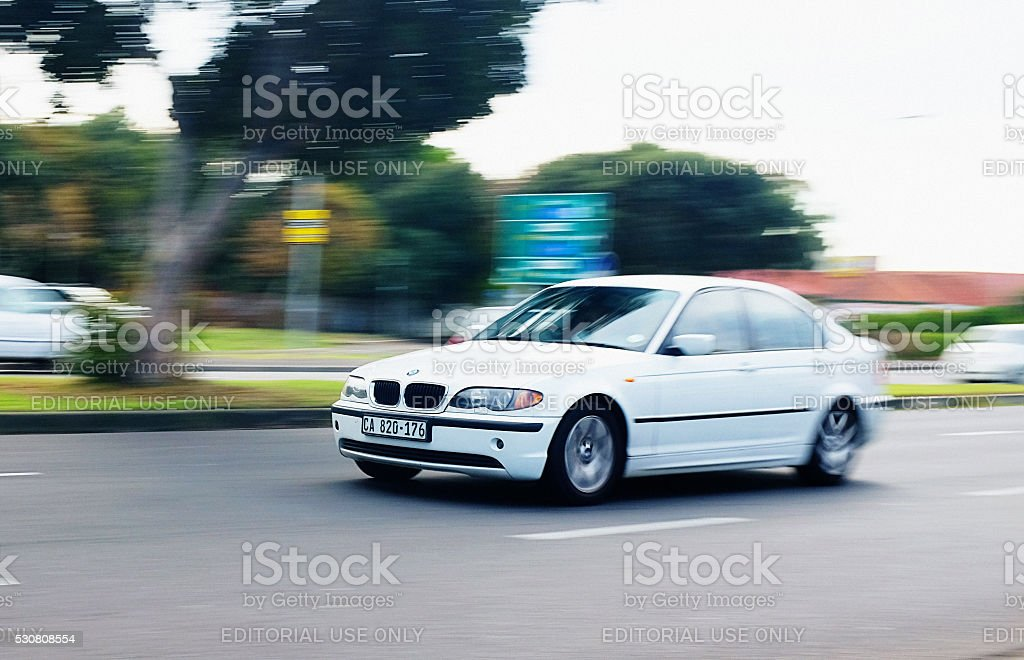 BMW 3-series passenger car drives down a suburban main road stock photo