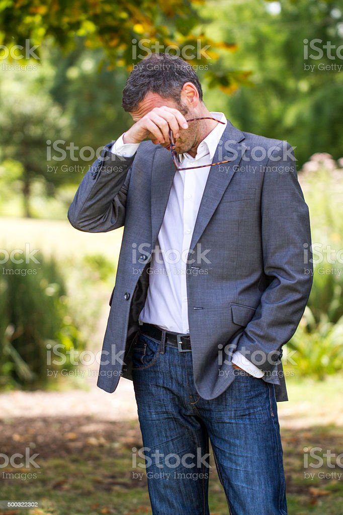 40s gray hair businessman having pollen allergies outdoors stock photo