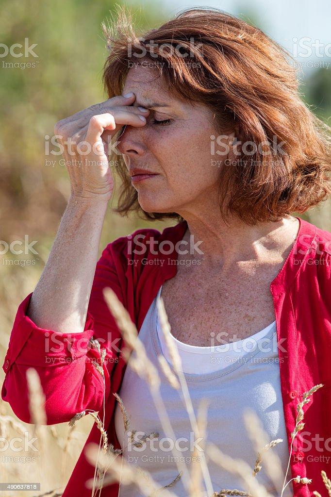 50s brunette woman having sinus and headache pain outdoors stock photo