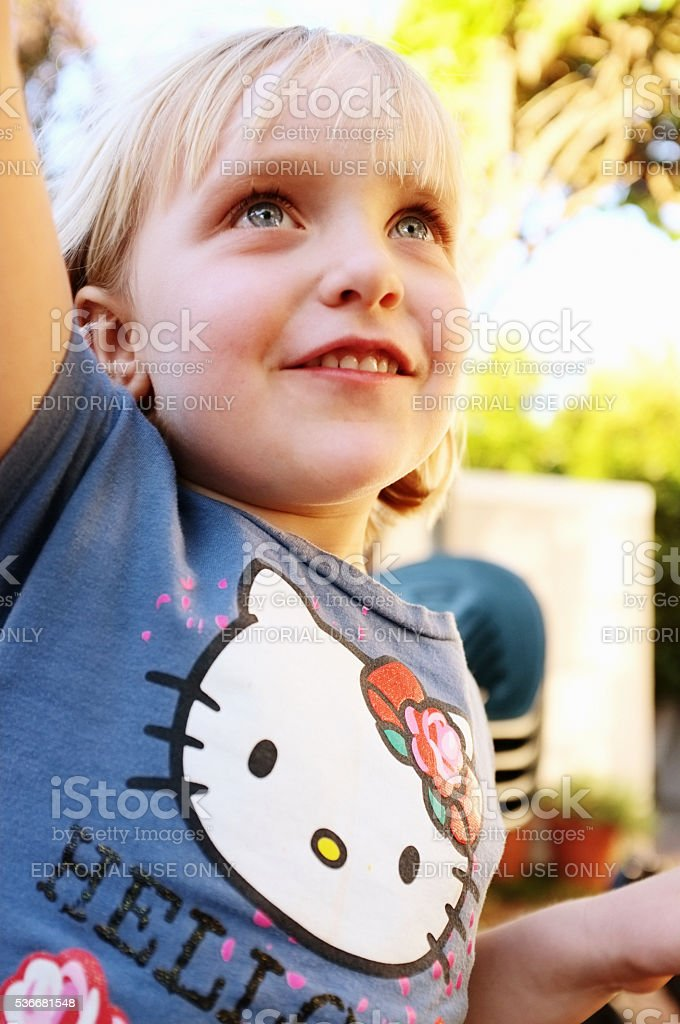 5-year-old blonde girl Hello Kitty T-shirt smiling Japanese stock photo