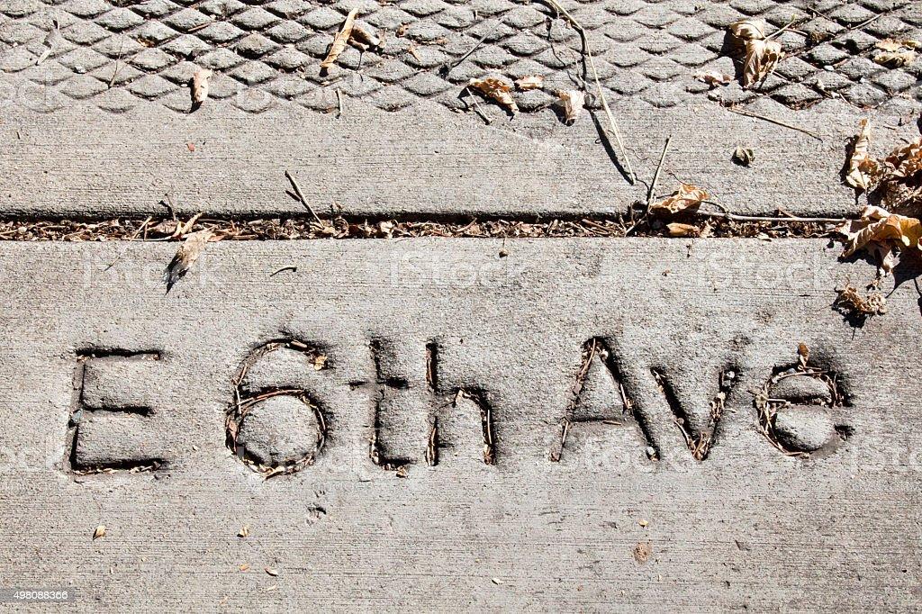 E 6th Ave in a concrete sidewalk stock photo