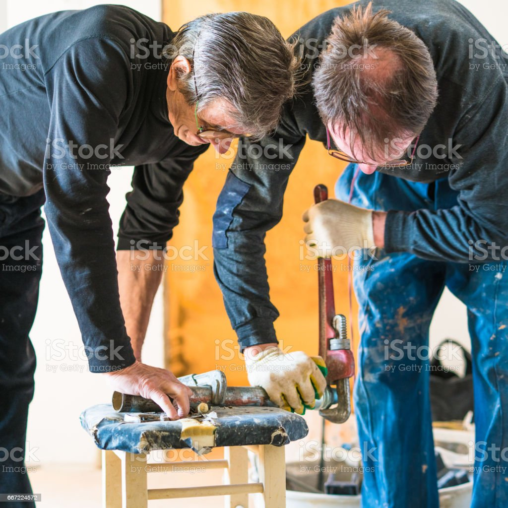 70-years-old active senior and 30-years-old men, construction workers - plumbers, working together for home renovation stock photo