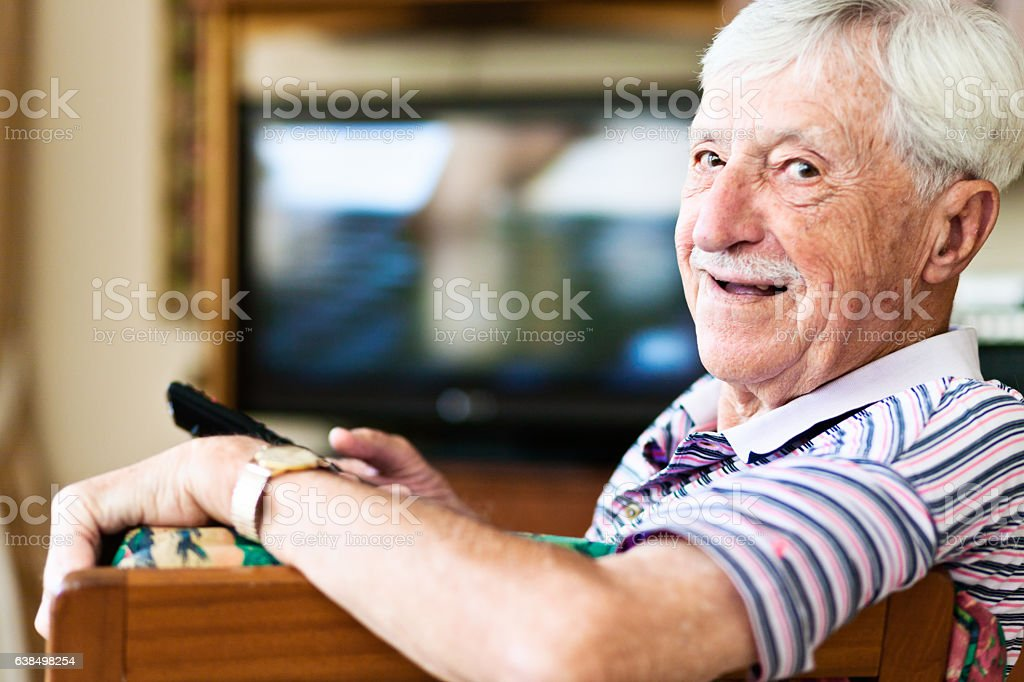 90-year-old man laughs; he's got the TV remote control! stock photo