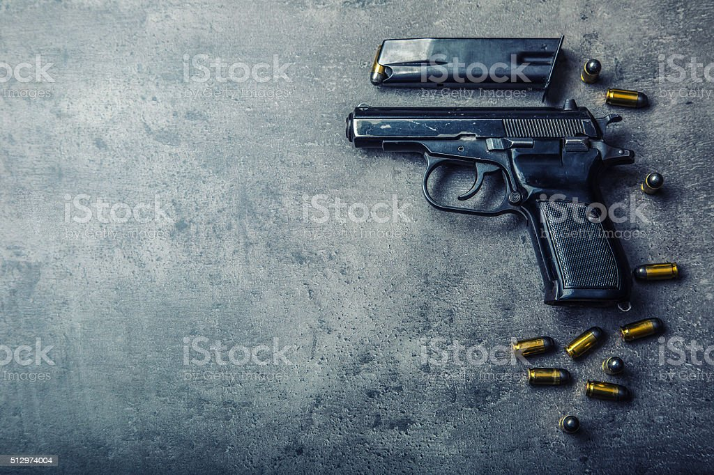 9mm pistol gun and bullets strewn on the table stock photo