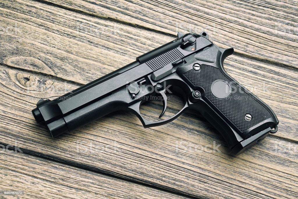 9mm pistol, Gun weapon series, Modern U.S. Army handgun M9 close-up on wooden background. stock photo