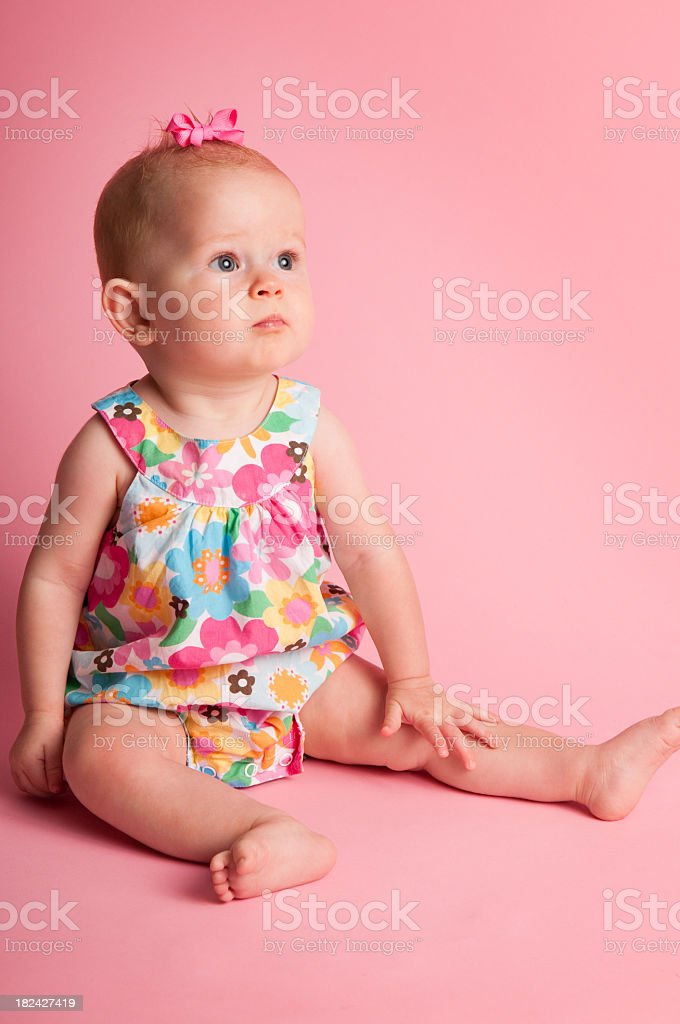 9-Month-Old Baby Girl Sitting on Pink Background royalty-free stock photo