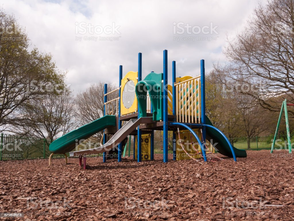 a close up shot of a metal slide in a child's playground with bark wooden chips for safety, accident, no people shining metal, dangerous and fun for children and parents stock photo