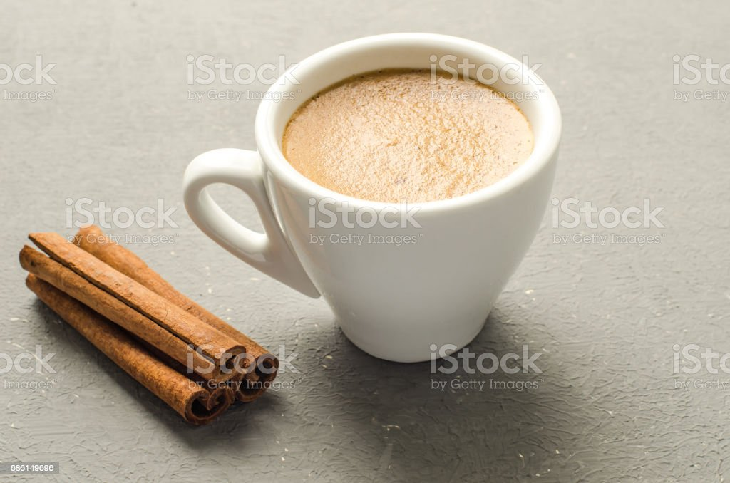 a cup of coffee and cinnamon stick on a grey background stock photo