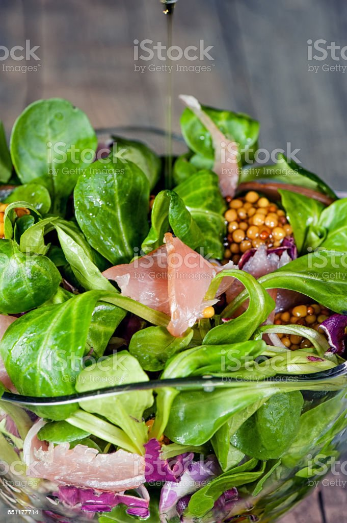 a dish of different types of colorful lettuce leaves, arugula, prosciutto ham, olive oil and Dijon mustard in glass transparent bowl stock photo