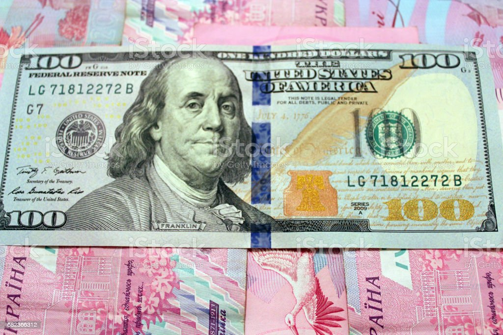 a hundred American dollars on the grivnas banknotes' background stock photo