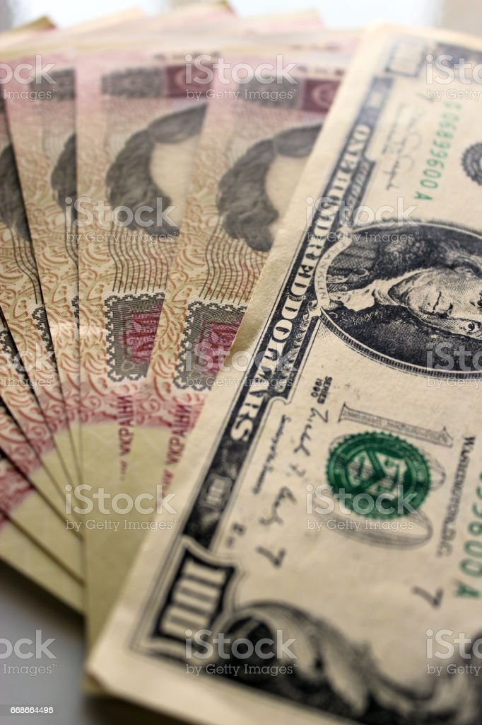 a hundred dollars laying on the Ukrainian grivnas stock photo