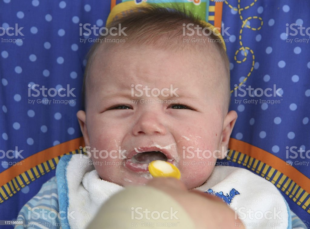 a little baby looking unimpressed with food royalty-free stock photo