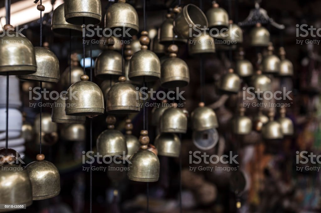 a lot of small  brass brass bells hanging in the small souvenir shop in the asia stock photo