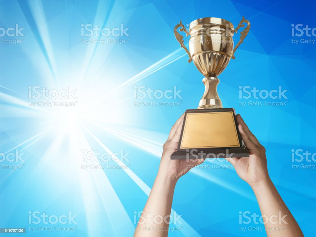 a man holding up a gold trophy cup with abstract blue light and modern background copy space ready for your trophy design. stock photo
