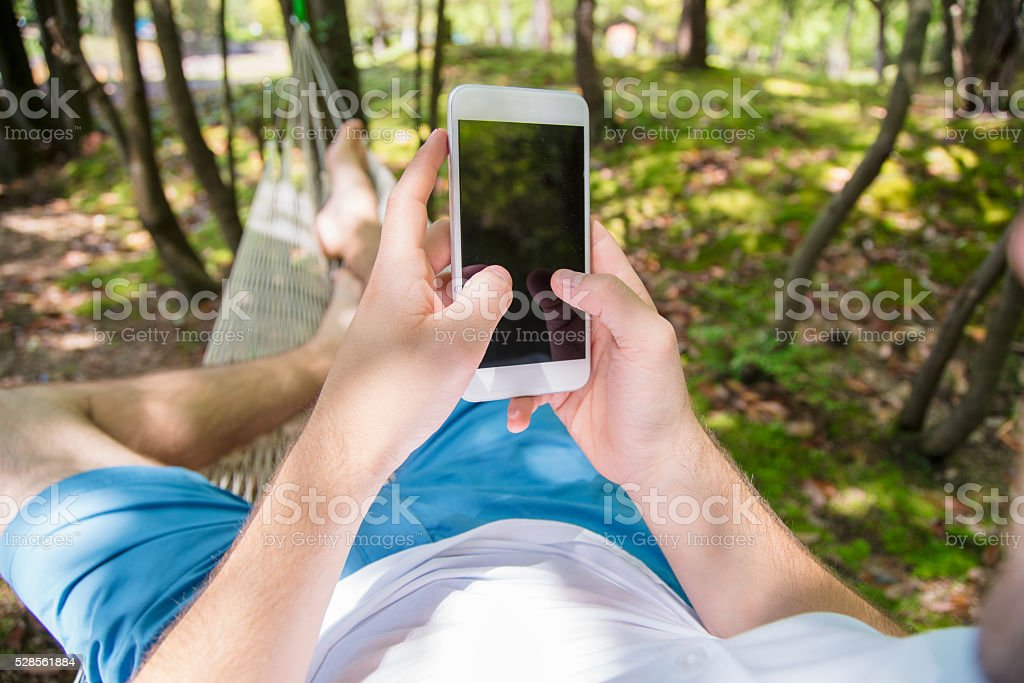 POV of a man in a hammock using a smartphone stock photo