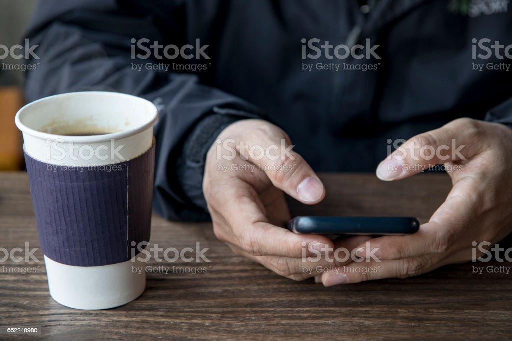 a man is using the smartphone on the table next to a cup of coffee stock photo