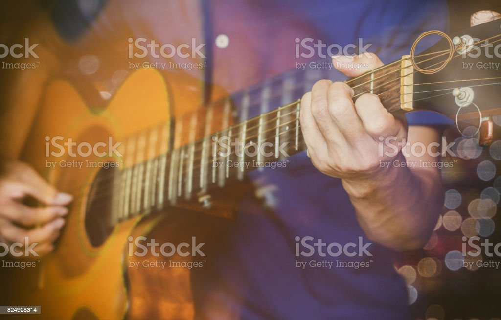 a man playing acoustic guitar with filter color tone and motion blur and bokeh background. stock photo